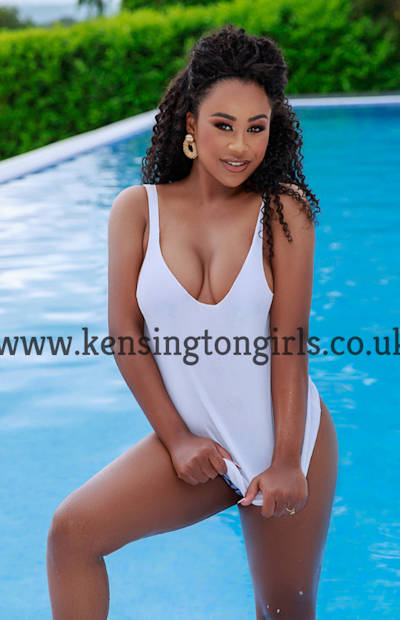 Black female companion in a white swimsuit standing by a swimming pool
