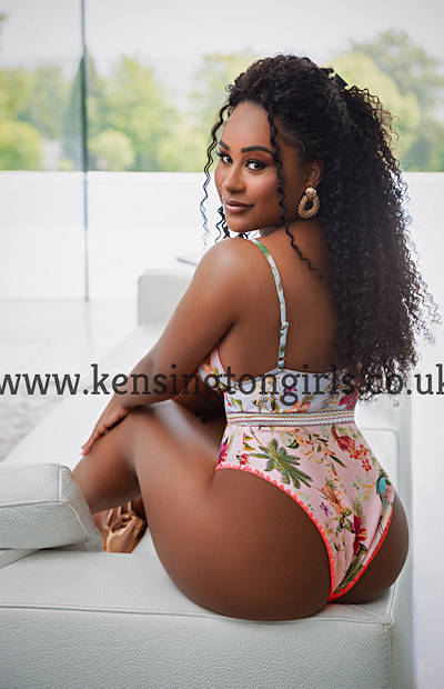 Ebony girl sitting on a sofa looking over her shoulder