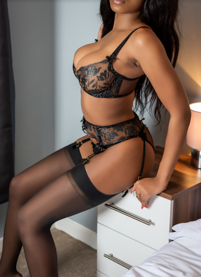 Sexy photo of a black girl in black suspenders and stockings lying on a bed